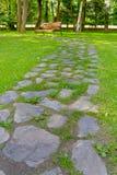 De weg van de steen in het park, dat naar een bank gaat. Royalty-vrije Stock Foto's