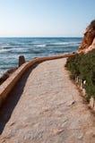 De weg van de steenbestrating langs rotsachtige kust. stock fotografie