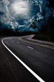 De weg van het asfalt en donkere donderwolken over het Stock Afbeeldingen