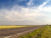 De weg van het asfalt met drammatic hemel Stock Afbeelding