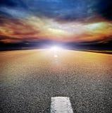 De weg van het asfalt op het gebied over stormachtige hemel Royalty-vrije Stock Foto's
