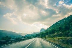 De weg van het asfaltspoor met een stormachtige donkere hemelachtergrond, Weg in Albanië na de regen Stock Foto's