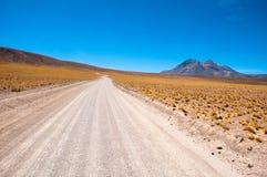De weg van het grint in Atacama woestijn, Chili Stock Foto's