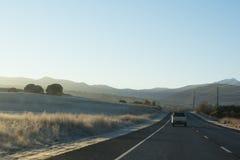 De weg van het land met auto's die naar bergen bij zonsopgang leiden Stock Foto