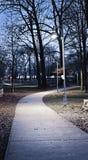 De weg van het park bij schemer stock afbeeldingen