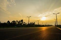 De weg van het plattelandsasfalt bij de zomerzonsondergang Royalty-vrije Stock Afbeeldingen