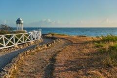 De weg van het toeristengrint met een witte omheining die tot de rotonde, op de oceaan leiden royalty-vrije stock afbeelding