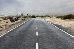 De weg van het woestijnasfalt met een typisch klein dorp van Lanzarote Eiland op de achtergrond, Canarische Eilanden stock afbeeldingen