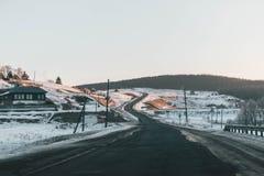 De weg verdwijnt achter de mooie jeneverbessenboom in het zonnige en ijzige de winterlandschap royalty-vrije stock fotografie