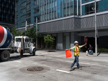 De weggaande bouwwerf van de cementvrachtwagen met flagger stock foto's