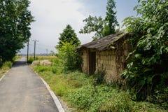 De wegkant dilapidated baksteen-ontworpen plattelandshuisje met aarden muur in wij royalty-vrije stock afbeelding