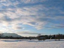 De Weide van de winter - Kerk en bergen Stock Foto