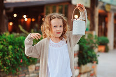 De welkom hetende gasten van weinig kindmeisje bij comfortabel avondbuitenhuis Stock Foto's