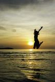 De welkome zonsopgang van de meisjessprong op het strand Stock Afbeelding