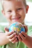 De wereld in jonge geitjeshanden stock foto