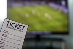 De Wereldbeker is op TV in de handen van een bookmaker van het kaartjesbureau, sporten weddend, close-ups stock foto's