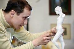 De werken van de beeldhouwer met concentratie in studio Royalty-vrije Stock Afbeeldingen