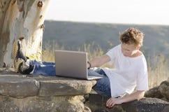 De werken van de kerel aangaande laptop Stock Fotografie