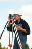 De werken van de landmeter met theodoliet Stock Fotografie