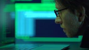 De werken van de softwareprogrammeur bij nacht, selectieve nadruk op gezicht stock videobeelden
