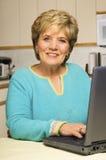 De werken van de vrouw aangaande laptop in keuken Royalty-vrije Stock Afbeelding