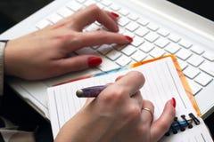 De werken van de vrouw aangaande witte laptop. stock afbeeldingen