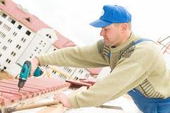 De werken van het dakwerk met schroevedraaier Stock Fotografie