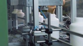 De werken van het installatiemateriaal met flessen met chemische producten op geautomatiseerde transportband stock videobeelden