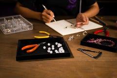 De werken van de juwelenontwerper aangaande een schets van de handtekening Royalty-vrije Stock Afbeelding