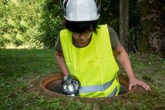 De werken van de rioolreparatie in het mangat door een vrouwenarbeider stock fotografie
