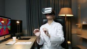 De werken van de vrouwenwetenschapper met virtuele werkelijkheidsglazen die in haar bureau zitten Wetenschap en onderzoekconcept stock footage
