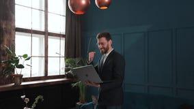 De werken van de zakenman aangaande laptop Hij slaagde internationaal door groot contract te winnen Hij is zeer gelukkig stock videobeelden
