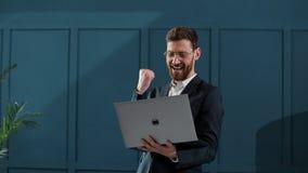 De werken van de zakenman aangaande laptop Hij slaagde internationaal door groot contract te winnen Hij is zeer gelukkig stock footage