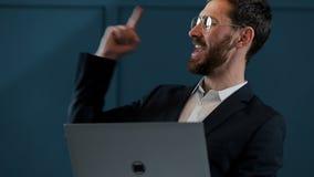 De werken van de zakenman aangaande laptop Hij slaagde internationaal door groot contract te winnen Hij is zeer gelukkig stock video
