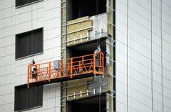 De werkende bouwer is op de lift en de werkzaamheden bij hoogte wanneer het beëindigen van het gebouw Royalty-vrije Stock Foto