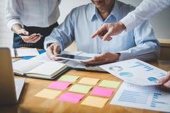 De werkende conferentie van Co, Commerci?le teamcollega's die het werk analyse bespreken met financi?le gegevens en de marketing  stock foto