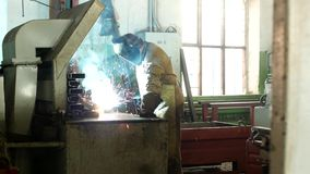 De werkende lasser bij de fabriek in een beschermend kostuum last het deel, maakt de lasser deel, de productie, licht stock videobeelden