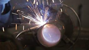 De werkende lasser verwerkt het metaal, voorbereidt de basis Een mens in een beschermend kostuum, vonken stock video