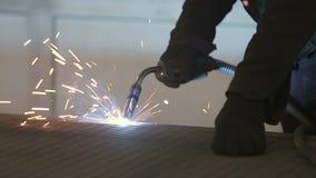 De werkende lasser verwerkt het metaal, voorbereidt de basis Een mens in een beschermend kostuum, vonken stock videobeelden