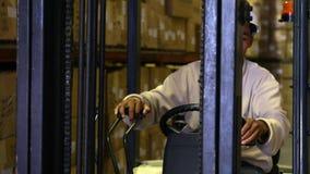 De werkende machine van de vorkheftruckbestuurder met dozen op het stock video