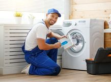 De werkende mensenloodgieter herstelt wasmachine in wasserij stock foto's