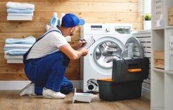 De werkende mensenloodgieter herstelt wasmachine in wasserij Stock Afbeeldingen