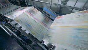 De werkende transportband beweegt gedrukte krant in een typografiefaciliteit stock footage