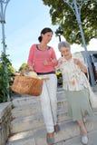 De werker uit de hulpverlening van het huis met bejaarde persoon in stad royalty-vrije stock foto