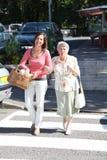De werker uit de hulpverlening van het huis met bejaarde persoon in stad Stock Afbeelding