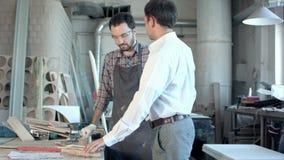 De werkgever betaalt de timmerman in workshop stock videobeelden