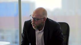 De werkgever is boos met zijn ondergeschikte werknemer in het bureau en het ontslag hem stock videobeelden