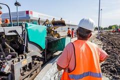 De werkgever is controlearbeiders op bouwwerf Vervoer hete asph Stock Afbeeldingen