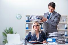 De werkgever die het extra werk brengen aan zijn hulpsecretaresse stock fotografie