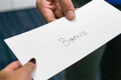 De werkgever geeft een bonus aan werknemer stock afbeeldingen